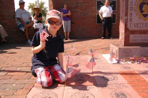 Caleb Waller sits next to his grandfather's plaque during a Memorial Day Ceremony at Laisley Park on Monday.