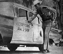 "Florida Highway Patrolman Ralph Moore , Tallahassee, Fla., stands by the cab driven by murder victim Adam William ""Bud"" Jenkins. Photo: Florida Memory Project"